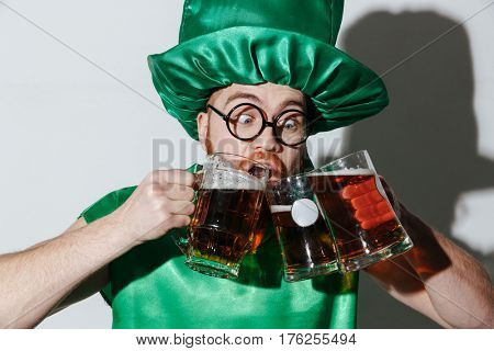 Funny man in st.patriks costume and eyeglasses which drinking beer from the many cups over gray background