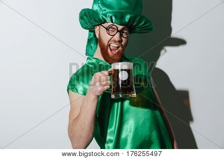 Drunk screaming man in st.patriks costume and eyeglasses which holding cup of beer over gray bakground