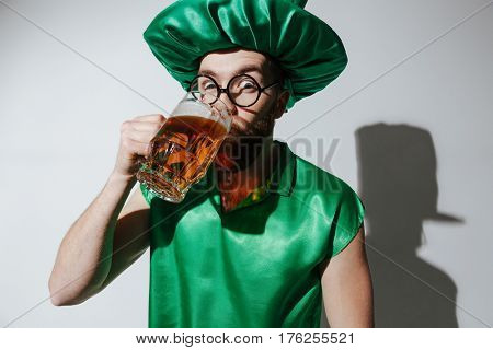 Surprised man in st.patriks costume and eyeglasses which drinking beer and looking at camera over gray background