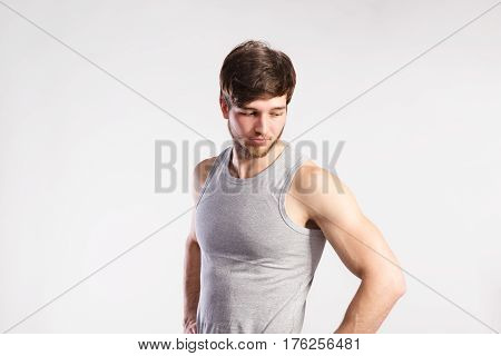 Handsome hipster fitness man in gray tank top shirt. Studio shot on gray background.
