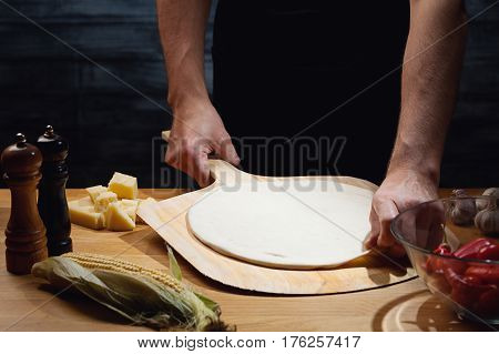 Chef cooking pizza, putting pizza base on board. Low key shot, close up of hands, some ingredients around on table.