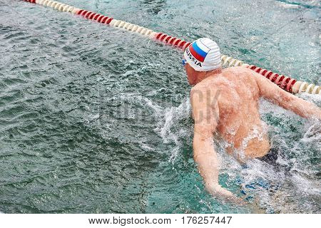 SAHYURTA IRKUTSK REGION RUSSIA - March 11.2017: Cup of Baikal. Winter Swimming Competitions. Butterfly. One man on the water path from back