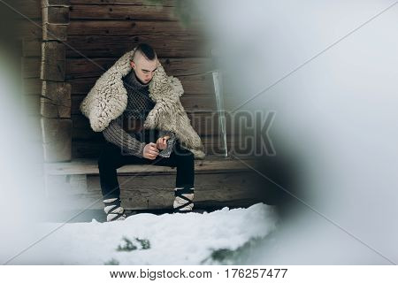 Brave Viking Warrior Sharpening Axe Before Battle In The North, Scandinavian Man With Mohawk Sitting