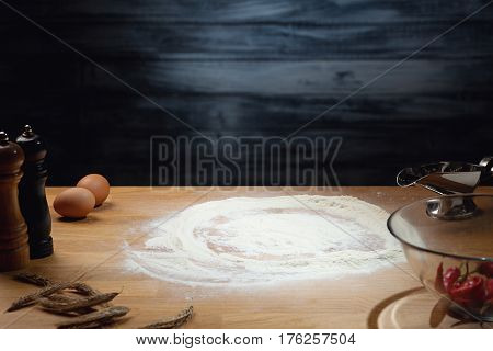 Cooking background flour on wooden table. Low key shot; light on flour; some ingredients around on the table. Copy space.