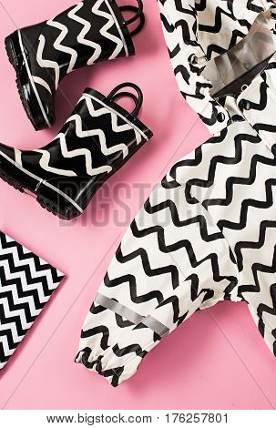 The Black and white rubber boots or gardening boots on pink studio background and raincoat