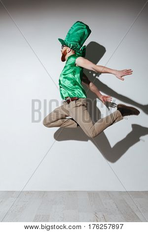 Vertical image of flying man in st.patriks costume. Side view. Isolated gray background