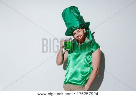 Smiling bearded man in green costume of st.patriks which holding cup of green beer and looking at camera. Isolated gray background
