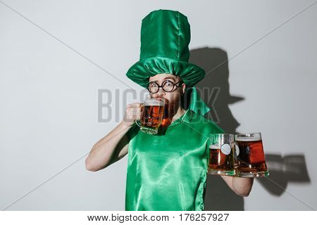 Man in st.patriks costume and eyeglasses which drinking beer and holding cups of beer in second hand. Isolated gray background