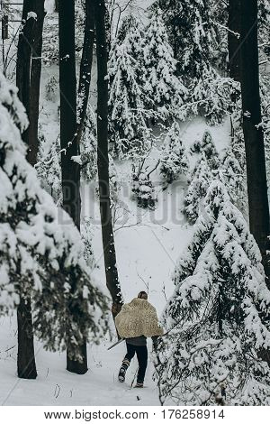 Viking Hunter In Pelt Walking In Snow Winter Forest With Steel Axe And Sword, Viking Warrior Hunting