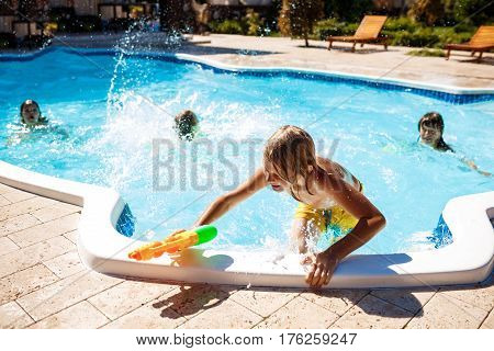 Cheerful children playing waterguns, rejoicing, jumping, swimming in pool. Copy space