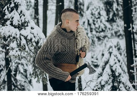 Portrait Of Strong Viking Warrior With Mohawk Haircut And Wolf Pelt Armor Holding Axe And Walking In
