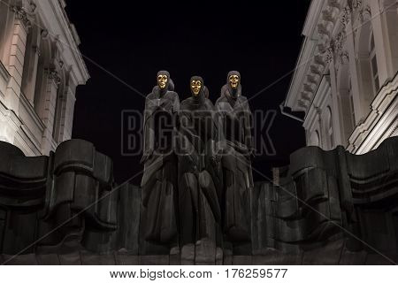 Vilnius Lithuania - january 08 2017: Vilnius Lithuania. Statues of Three Muses on Lithuanian National Drama Theatre at night. National Drama Theatre in Vilnius on Gediminas Avenue. Main entrance. Dramatic night background sets the mood.