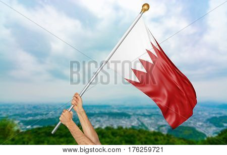 Young man's hands proudly waving the Bahrain national flag in the sky, part 3D rendering