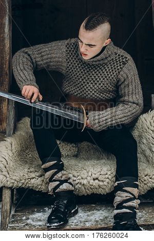 Portrait Of Strong Viking Warrior Sharpening His Sword, Scandinavian Viking Cosplay, Medieval Warrio