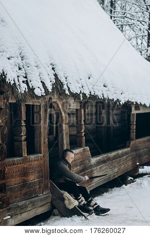 Viking Warrior Sharpening His Sword While Sitting Near Ancient Wooden Castle, Scandinavian Knight Wi