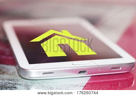 Real estate symbol on the cell phone screen . The concept of online real estate sales