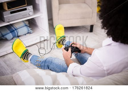 Happy man in yellow crocks enjoying free time. Hipster man sitting on sofa and playing computer games in front of television of laptop computer. Computer games concept.
