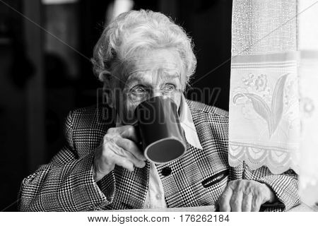 Elderly woman drinking tea. Black-and-white photo.