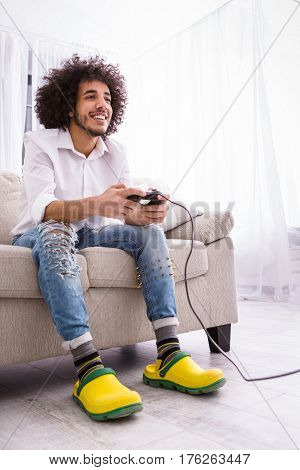 Young hipster handsome bearded man sitting on couch at home, playing video game on laptop computer while holding joystick. Happy, smiling, fun, entertainment, hands close up, details.