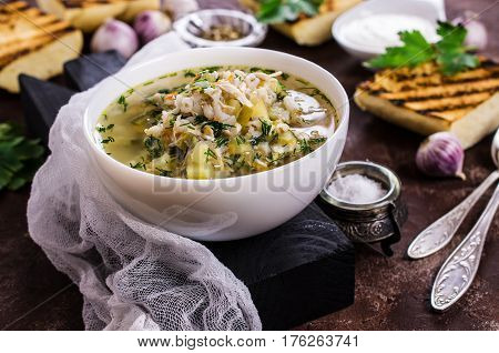 Thick meat soup with pearl barley and vegetables. Selective focus.