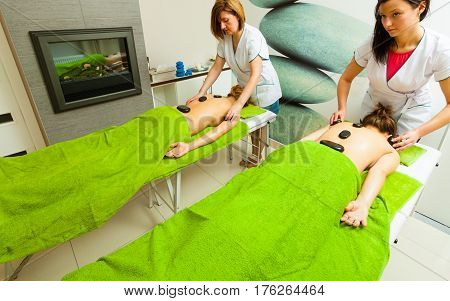 Spa relaxation healthy pleasure concept. Two women lying on stomach having massage with hot rocks stones in beautician