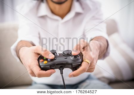 Closeup of hipster man holding joystick while playing computer games in front of laptop computer or television. Computer games concept.