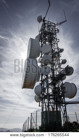 Detailed view of communication tower backlit against sun, dark tower