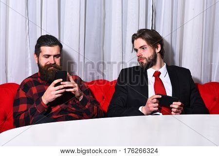 bearded men businessmen long beard brutal caucasian hipster with moustache hold mobile or cell phone has smiling face unshaven guys with stylish hair in suit red tie and checkered shirt