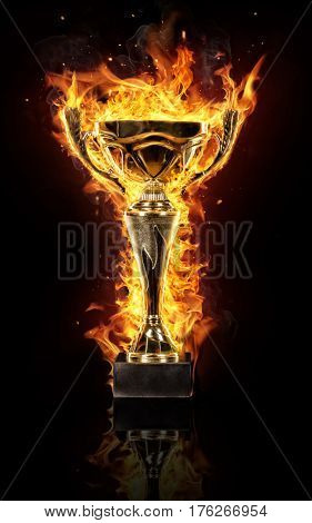 Burning gold trophy cup isolated on black background, flames around. Concept of success and effort.
