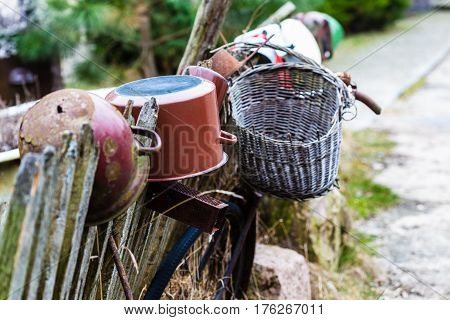 Oldfashioned vintage village details design concept. Old wooden fence with pots and wicker baskets on it.