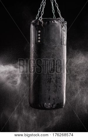 Monochrome photo of punching bag in empty room filled with smoke