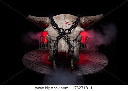 Chained cow/bull skull with red inner glow and smoke, standing on old grey wooden plate, with strong biker vibes.