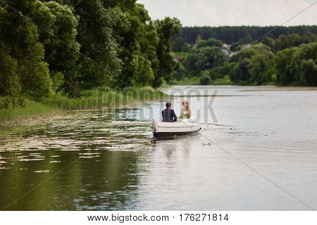 The groom and bride are floating on the river on the white boat