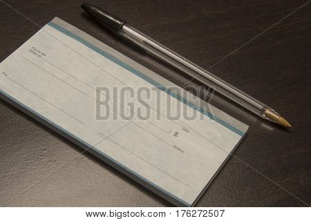 writing instrument with a book of checks to pay bills