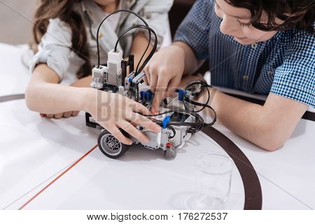 Gifted young generation. Clever skilled involved children sitting in the laboratory and creating robot while studying