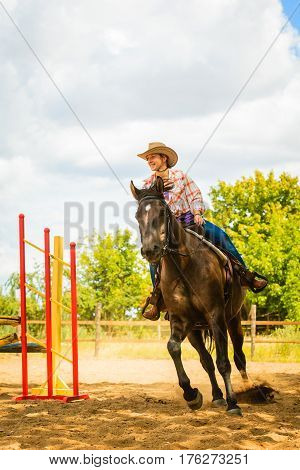 Taking care of animals horsemanship western competitions concept. Cowgirl in cowboy hat doing horse jumping through hurdle on sunny day