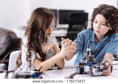 Process of discussion. Curious inventive skilled pupils sitting at school and having science class while expressing curiosity and working with robot