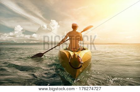 Woman in bikini exploring calm tropical beach by canoe. Travel and active lifestyle happiness emotion summer holiday concept.