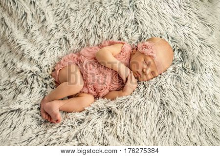 Close-up of a sleeping newborn girl a few days old. Newborn girl sleep in a pink tank tops and handmade bandage on her head on a fur rug. Ideas for newborn photo shoot