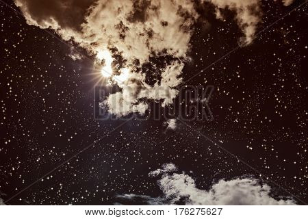 Amazing dark night sky with many stars bright full moon and cloudy. Outdoor at nighttime with moonlight. Pretty nature use as background. Vintage effect tone.