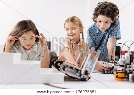 Robot test. Attentive joyful motivated kids sitting at school and testing cyber robots while working on the tech project