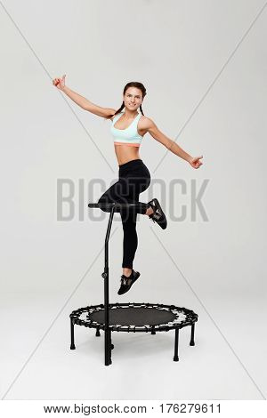 Young woman on mini rebounder jumping up showing thumbs up with smile isolated on grey