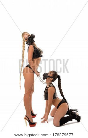 Two sexy girls in bdsm masks and leather underwear posing in studio one of them staying on ger knees with chain collar over her neck