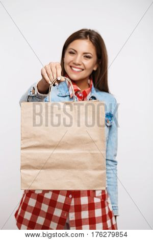 Pretty young woman in trendy check dress holding paper bag and smiling looking straight