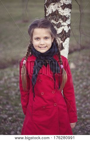 smiling child girl in red raincoat lean on birch tree stem