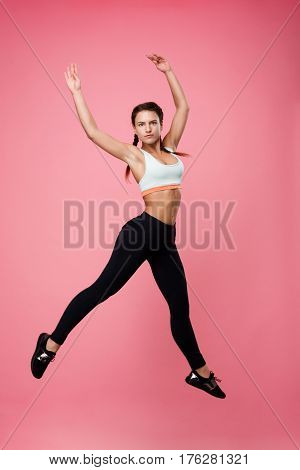 Pretty young sporty woman in blue top and black leggins jumping as ballerina looking straight