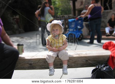 child sitting pacified girl sat bench hat toddler baby
