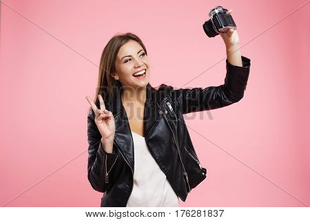 Young woman taking selfie on old roll-film camera, showing peace sign isolated on pink