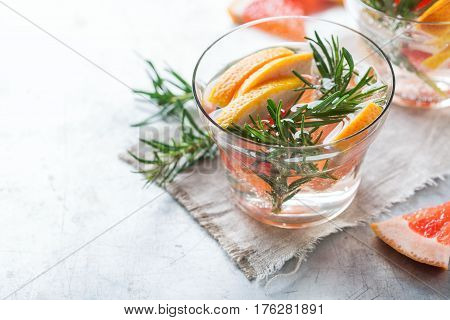 Healthcare, fitness, healthy nutrition concept. Fresh cool grapefruit rosemary infused water, cocktail, detox drink, lemonade for spring summer days. Copy space background