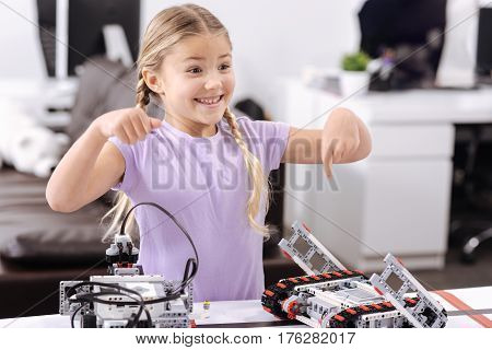 Look at this robot. Joyful smiling optimistic girl standing at school and demonstrating cyber robot while expressing positivity